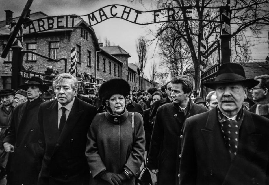 Polen, Auscwitz, 27-01-1995 Prins Claus, Koningin Beatrix en Prins Philip van Belgie lopen onder de poort door met de nazi-leus 'Arbeit Macht Frei'.