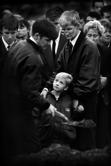 Noord-Ierland, Belfast, oktober 1993. Zilveren Camera 1993. Begrafenis Mark Rodgers(28). De vuilnisman kwam om het leven doordat extremisten van de protestantse zijde het vuur hadden geopend toen hij de loods wilde openen aan het begin van zijn shift. Hij dook weg onder een vrachtwagen maar een afketsende kogel trof hem in het hart. Hij liet met leven met nog een collega, James Cameron(58). Op de foto zijn familie met centraal zoontje Mark(8).